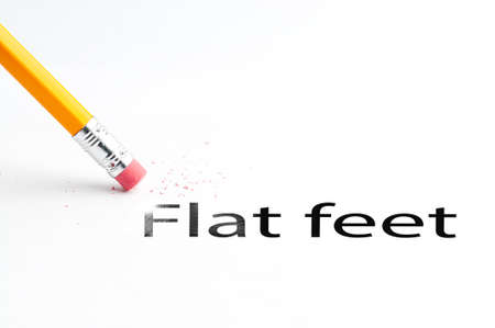 orthopaedist: Closeup of pencil eraser and black flat feet text. Flat feet. Pencil with eraser. Stock Photo