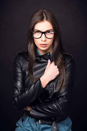 high size: Beautiful young woman. Girl in blue overalls, wearing glasses and a leather jacket. Sexy girl. High resolution photo. Hd images. Big size. Toned image Stock Photo
