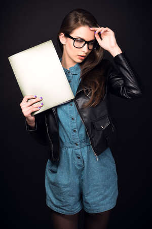 high size: Beautiful young woman. Girl in blue overalls, wearing glasses and a leather jacket. Woman with folders. Sexy girl. High resolution photo. Hd images. Big size. Toned image