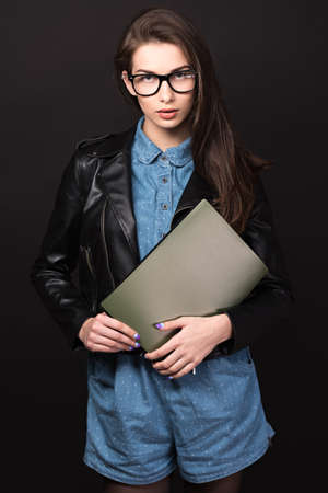 high size: Beautiful young woman. Girl in blue overalls, wearing glasses and a leather jacket. Woman with folders. Sexy girl. High resolution photo. Hd images. Big size. Stock Photo