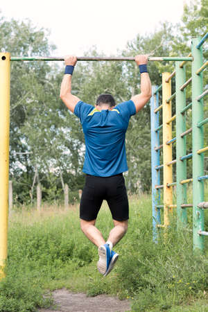 Strong young athlete. Strong young athlete is engaged in on an abandoned sports field. Pull-up on the bar. Athlete Outdoors.