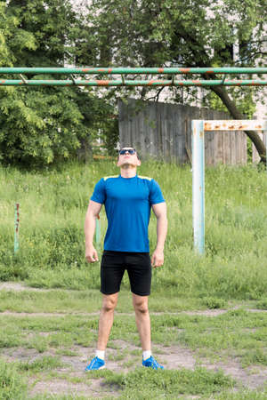 engaged: Strong young athlete. Strong young athlete is engaged in on an abandoned sports field. Pull-up on the bar. Athlete Outdoors.