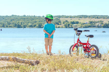 Kid with a bicycle near the river. Child with his beloved bike. Kid in a helmet stands next to bicycle. Beautiful baby. Toned image. Stock Photo
