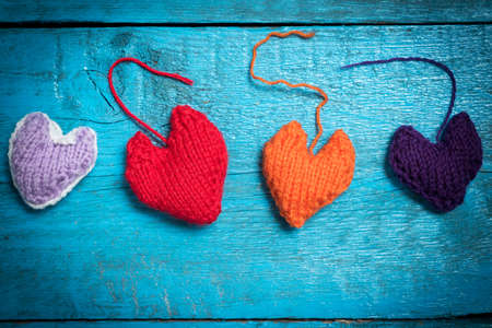 Valentines Day. Colorful knitted hearts. Red heart on the blue boards. Valentines day. Heart pendant. Red heart. Valentine cards. Space for text. Eighth of March. International Womens Day.