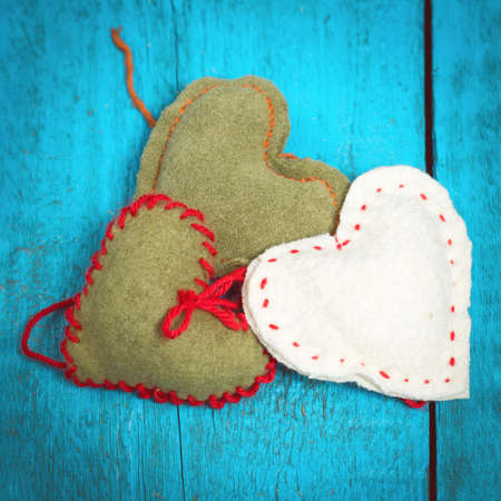 Colorful knitted hearts on the blue boards Stock Photo