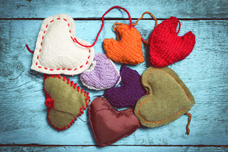 Colorful knitted hearts on the light blue boards