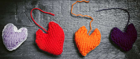 Colorful knitted hearts on the dark boards