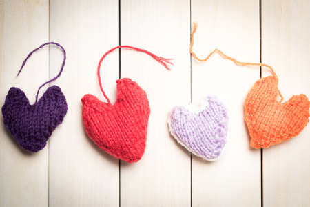 Colorful knitted hearts on light, wooden boards Stock Photo