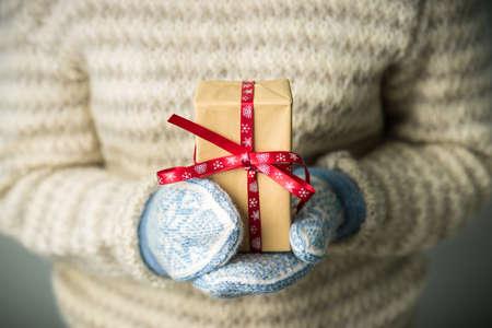 Een meisje met een doos met een kerstcadeau