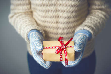 A girl holding a box with a Christmas present Archivio Fotografico