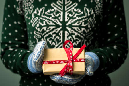 Christmas background. Girl is holding a Christmas present. Gifts for men. Merry Christmas. Gift for a girl. Sweater with Christmas ornament. Knitted dress. Box with gifts. Image in a dark key.