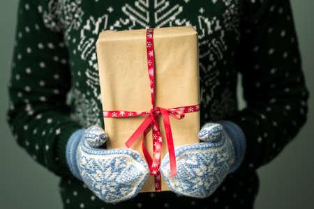 Vánoční pozadí. Dívka drží vánoční dárek. Dárky pro muže. Veselé Vánoce. Dárek pro dívku. Svetr s vánoční ozdobou. Pletené šaty. Box s dárky. Obrázek v tmavém klíči. Reklamní fotografie