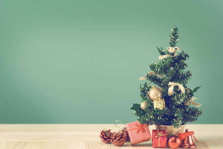 Festive Christmas tree stands on light boards. Christmas background. Christmas decorations on a green background. Space for text. New Years background. Toned image. Stock Photo