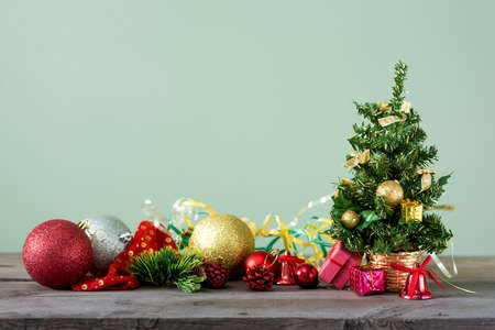 Christmas background. Little Christmas tree with decorations on a light wooden table. Green background. Space for text. New Years background.