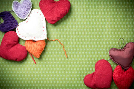 Valentines Day. Colorful knitted hearts on a vintage background in polka dots. Red heart. Green background. Valentines day. Heart pendant. Valentine cards. Eighth of March. International Womens Day.
