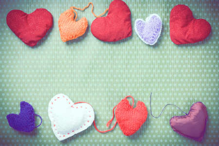 Valentines Day. Colorful knitted hearts. Valentines day. Heart pendant. Vintage background in peas. Red heart. Handmade Hearts. Valentine cards. Space for text. Toned image.