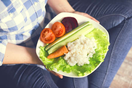 A girl holds a plate with rice and vegetables