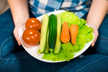 Girl with a plate of vegetables in hands. Healthy eating concept. A girl in jeans and a plaid shirt. Proper nutrition. Diet. Health. Vegetarian food. Vegans food.