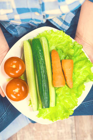Girl with a plate of vegetables