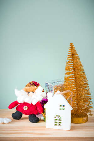 Christmas background. A small gold Christmas tree and boxes with gifts on a wooden table. Green background. Space for text. New Year's background.
