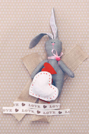 Valentines day. Tilde rabbit lying in a pile of handmade hearts. Valentine Day. Heart pendant. Space for text. Red Hearts. Image toned in trendy color.
