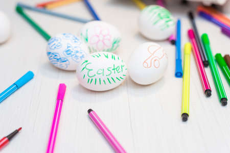 Easter eggs are on the table with colored felt-tip pens.. Easter ideas. Space for text. Egg tray. Happy easter.