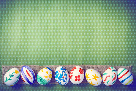 Painted Easter eggs on a green background with white polka dots. Toned image. Beautiful holiday card. Space for text. Happy easter.