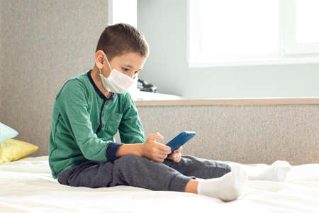 Stay at home quarantine coronavirus pandemic prevention. A child from boredom plays at home on the phone during quarantine. Prevention epidemic. COVID-19.