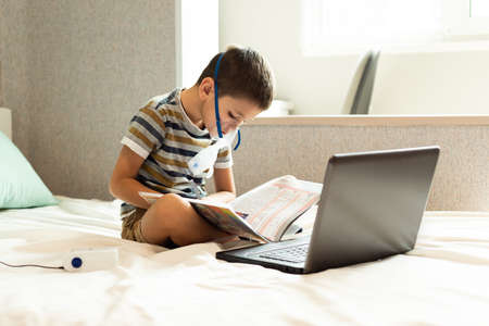 Stay at home quarantine coronavirus pandemic prevention. A child learns home lessons in an oxygen mask with a nibulizer, laptop and a book during quarantine. Prevention epidemic. COVID-19.