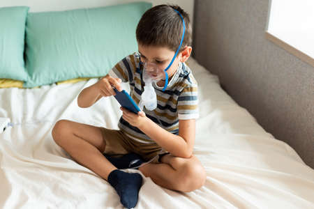 Stay at home quarantine coronavirus pandemic prevention. A child in an oxygen mask with a nibulizer plays on a mobile phone during quarantine. Prevention epidemic. COVID-19.