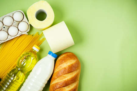Essential fresh products lie on a green background. Eggs, greens, spaghetti, sunflower oil, bread, milk, toilet paper, cookies. Food delivery covid-19 epidemic, Donation. top view. Copy space.
