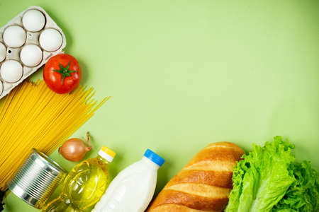 Essential fresh products lie on a green background. Eggs, greens, spaghetti, tomatoes, bread, milk, cookies, canned food. Food delivery covid-19 epidemic, Donation. top view. Copy space.