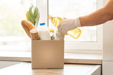Donation box with food on a light interior background. Stock Photo