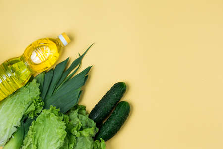 Essential fresh products lie on a yellow background. Greens food. Food delivery covid-19 epidemic, Donation. Top view. Copy space.