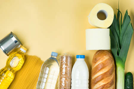 Essential fresh products lie on a green background. Eggs, greens, spaghetti, tomatoes, bread, milk, toilet paper, cookies, canned food. Food delivery covid-19 epidemic, Donation. top view. Copy space.