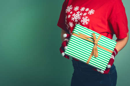Girl holding a box with a gift for Christmas .