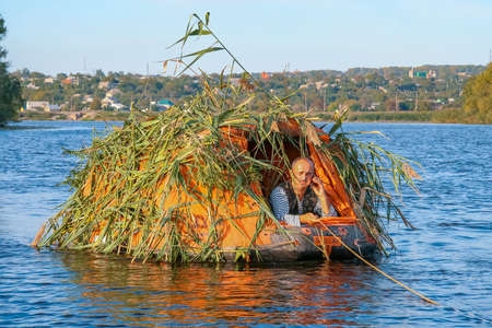 The hunter disguised himself in a floating ambush for bird hunting. Dnipro river near the village of Kushugum, Zaporizhzhya region, Ukraine. September 2012 Редакционное