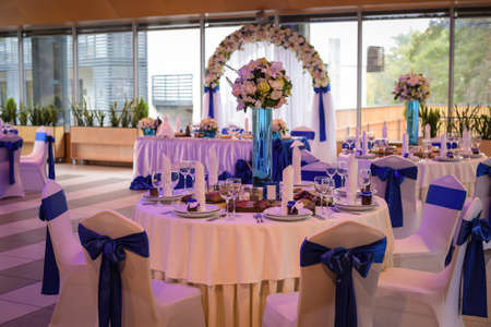 wedding decoration, table with beautiful flowers and a lot of dishes chairs with blue bows in the restaurant