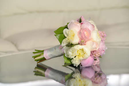 wedding bouquet, peonies shaped roses on a glass table with reflection