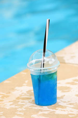 blue summer cocktail in plastic glass with straw near the pool on background of bright turquoise water