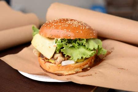 tasty grilled beef burger with lettuce and cheese served on pieces of brown paper on wooden table, street food