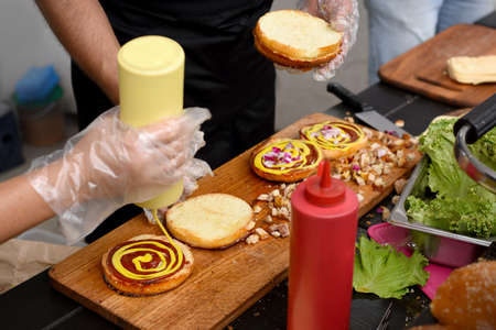 chef and his assistant adding mustard and ketchup to burgers grilled for outdoors barbecue