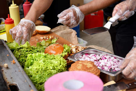 street food, process of cooking beef burgers outdoors on open kitchen