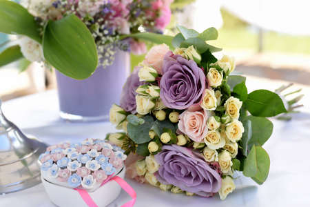 bridal bouquet with purple roses on the table with a porcelain box in the shape of a heart, wedding decoration elements