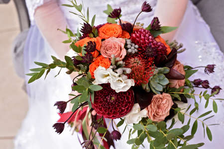 bride holding in hands bright wedding bouquet with claret dahlias orange and cream roses Zdjęcie Seryjne