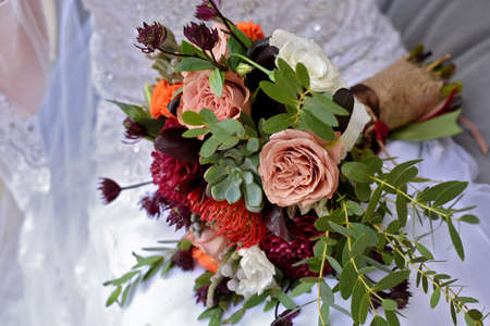 wedding bouquet with claret dahlias orange and cream roses