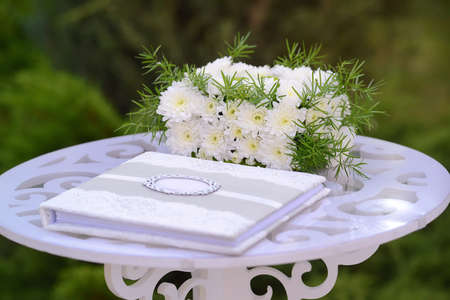 wedding elements, guest book and gift box of flowers on white carved wooden table Zdjęcie Seryjne