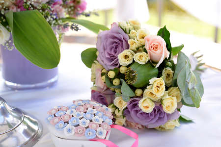 wedding bouquet with purple roses on white table with a porcelain jewelry box in the shape of a heart