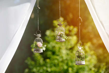 decorative cages with flowers for wedding ceremony on a sunny day