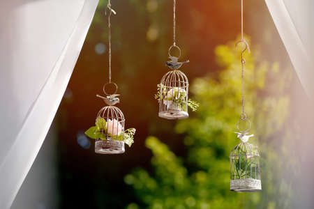 small cages for birds in the sun as a decoration for wedding ceremony